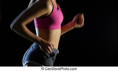 Female athlete running on a black background from the side....