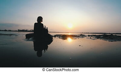 Silhouette of a Child on the Beach Building a Sand Castle at...