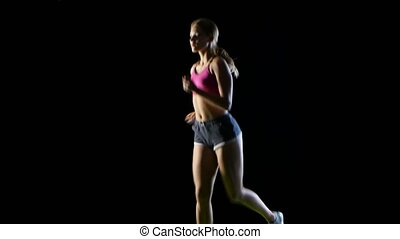 Athletic fitness woman running front view on a black...
