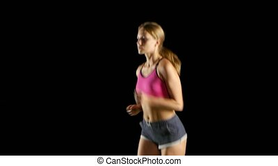 Athlete in sports clothes running lightly on a black screen....