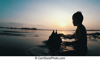 Silhouette Little Boy Builds a Sand Castle at Sunset. Happy...