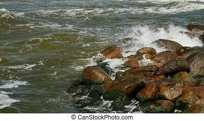 Seawater splashing on seashore rocks. - Nature background....