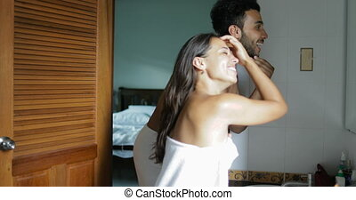 Couple In Bathroom Woman Washing Face Talking To Man In...