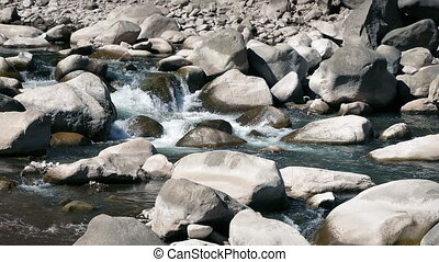 Rocky River On Sunny Day - River through large rocks in the...
