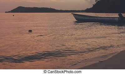 Local wooden boat near the beach during sunset . Dusk at Gam...