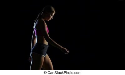 Girl goes leading a healthy lifestyle on a black background....