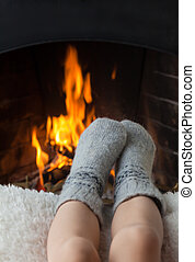 Childrens feet are heated in the fireplace - Childrens feet...
