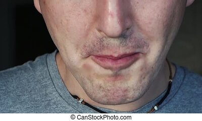 close up footage of a male mouth eating a sandwich indoores