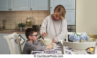 child drinks milk - Mother pours milk into a mug and gives...