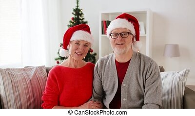 senior couple recording christmas video greeting -...