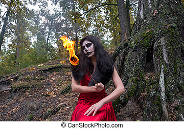 Brunette woman with makeup like a Halloween skull sits with...