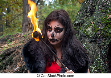 Woman with makeup like a Halloween skull sits with a torch...