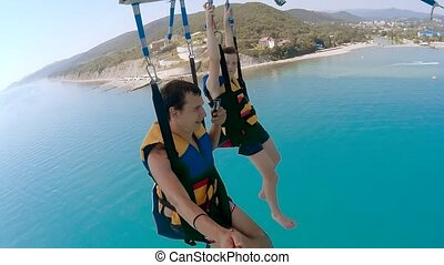 paragliding and parasailing ocean lifestyle. man and boy are...