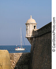 Sailing boat departing bay before Portuguese fortress...