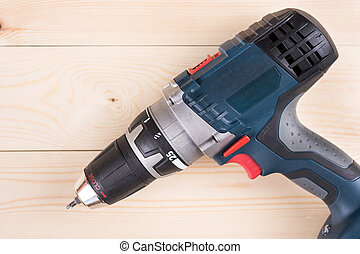 Flat lay cordless drill on the wooden boards with copy...