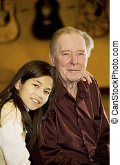 Elderly man sitting with granddaughter