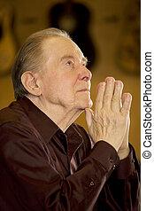 Elderly man praying in church - Elderly man looking up while...