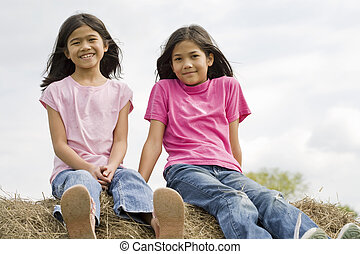 two young girls sitting on top of haybale - two young girls...