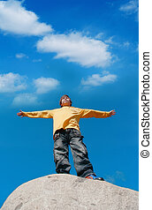 move apart hands - The teenager standing on a stone with...