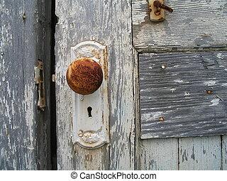 Old doorknob ajar - Rusty door handle in an industrial area.