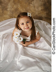Little girl trying on mommys wedding dress - Beautiful young...