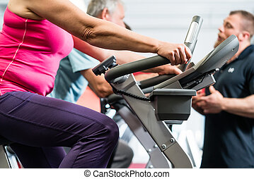 Seniors spinning with personal trainer at the gym for better...