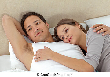 Pensive couple lying in each others arms on their bed
