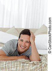 Portrait of a cheerful man lying on his bed at home