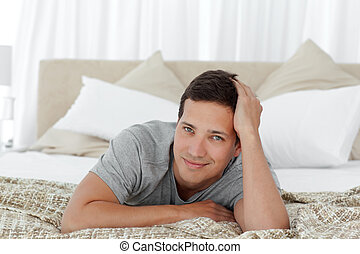 A happy man relaxing on his bed