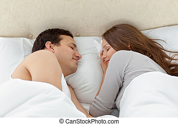 Serene couple sleeping together on their bed at home