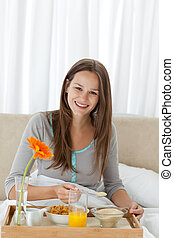 Cute woman having breakfast on the bed