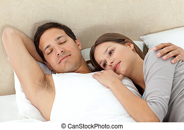 Serene woman lying on her boyrfriends arms while sleeping in...