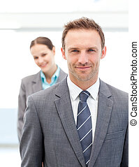 Two smiling business people posing in a row at work
