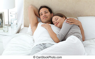 Man dreaming on his bed while relaxing with his girlfriend