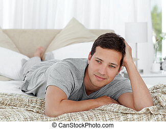 Thoughtful young man lying on his bed at home