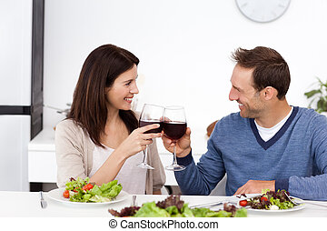 Lovely couple clinking glasses of red wine during lunch in...