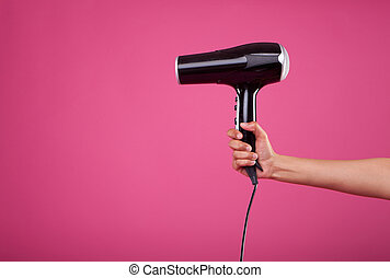 hairdryer - woman hand holding hair dryer on pink background