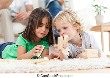 Little boy and girl playing with dominoes together in the...