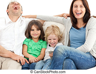 Family laughing while watching tv