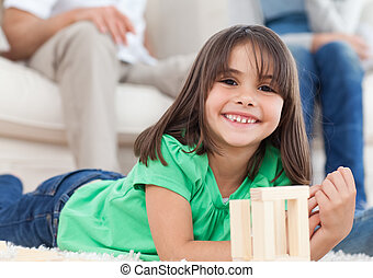 Cute little girl playing with dominoes in the living room