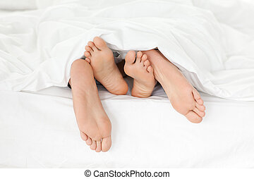 Close up of couple's feet while having fun in their bed at...
