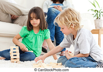 Cute brother and sister playing with dominoes on the floor