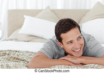 Cheerful man lying in his bedroom at home