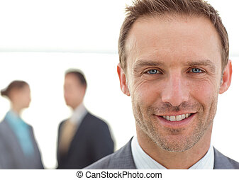 Cheerful businessman posing in front of his team while...