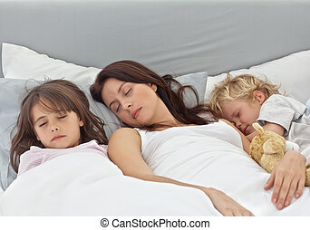 Adorable children sleeping with their mother on her bed at...