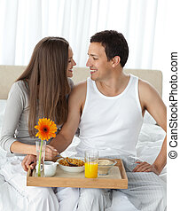 Passionate couple with their breakfast sitting on the bed
