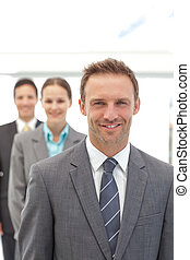 Three happy business people posing in a row in the office