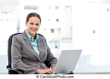 Young manager working on the laptop sitting at her desk in...