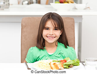 Portrait of a little girl eating pasta and salad in the...