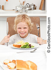 Portrait of a little boy ready to eat pasta and salad in the...
